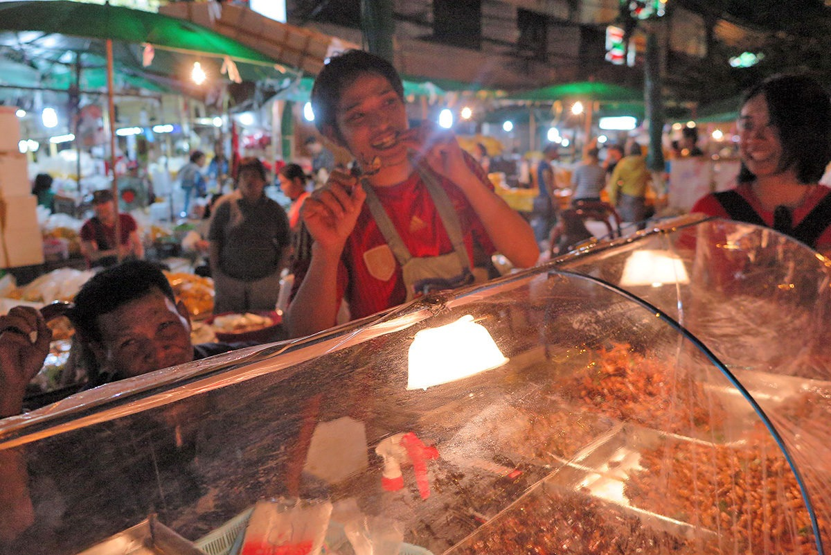 If you have no idea how to eat that grasshopper, the vendor will gladly show you! - street food in Bangkok
