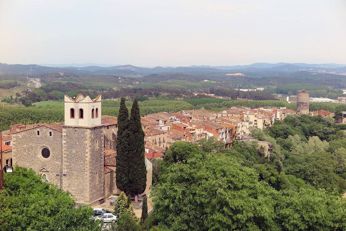 Hostalric town, with the church in the foreground and Frares tower in the background