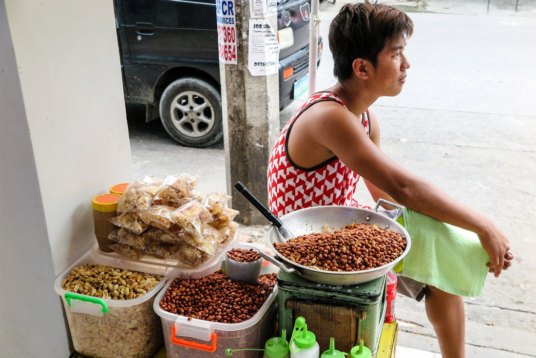 A man selling fried peanuts at Tacloban street market