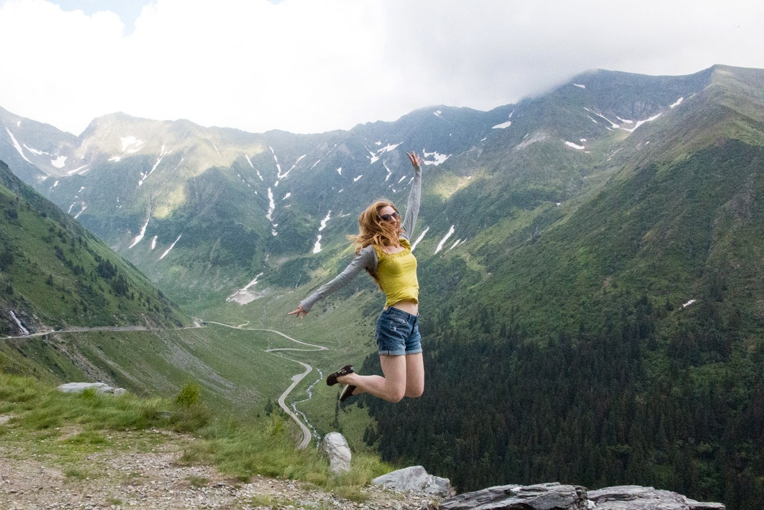 Veronika of TravelGeekery jumping above Transfagarasan Road