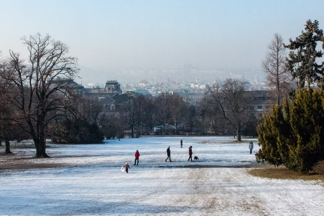 A small hill in a snowy Riegrovy Sady park serving as a fun slide for the kids!