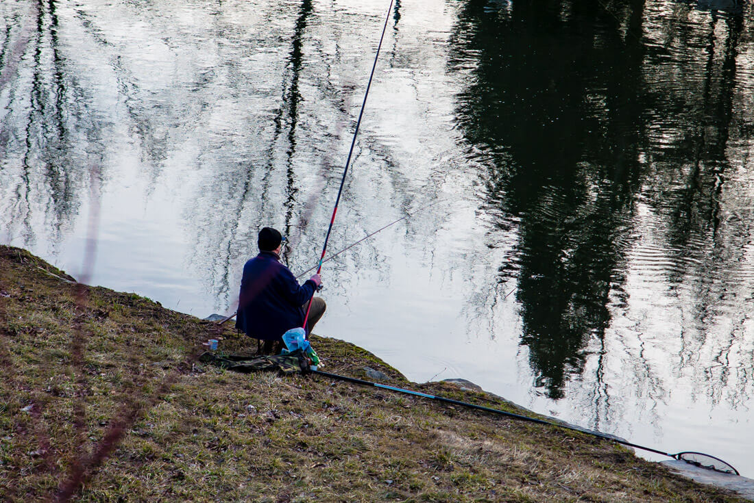 A fisherman fishing in the Ostravice River, near Ostrava city center
