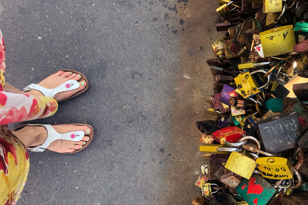 Closeup of feet in flip flops with love locks on a bridge