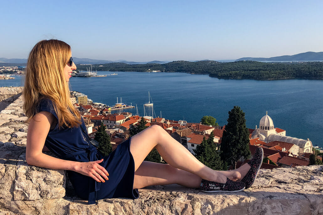 A woman sitting on a wall with a view of Sibenik City, Croatia