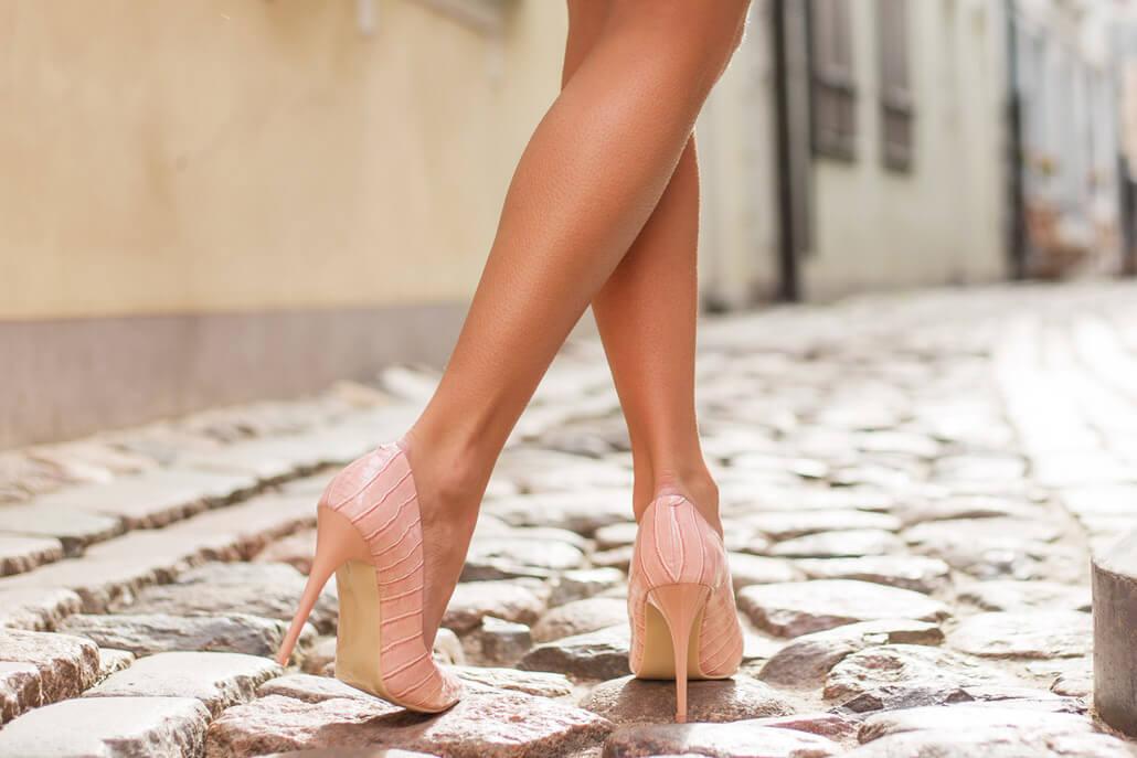 Woman on high heels walking on cobblestone streets