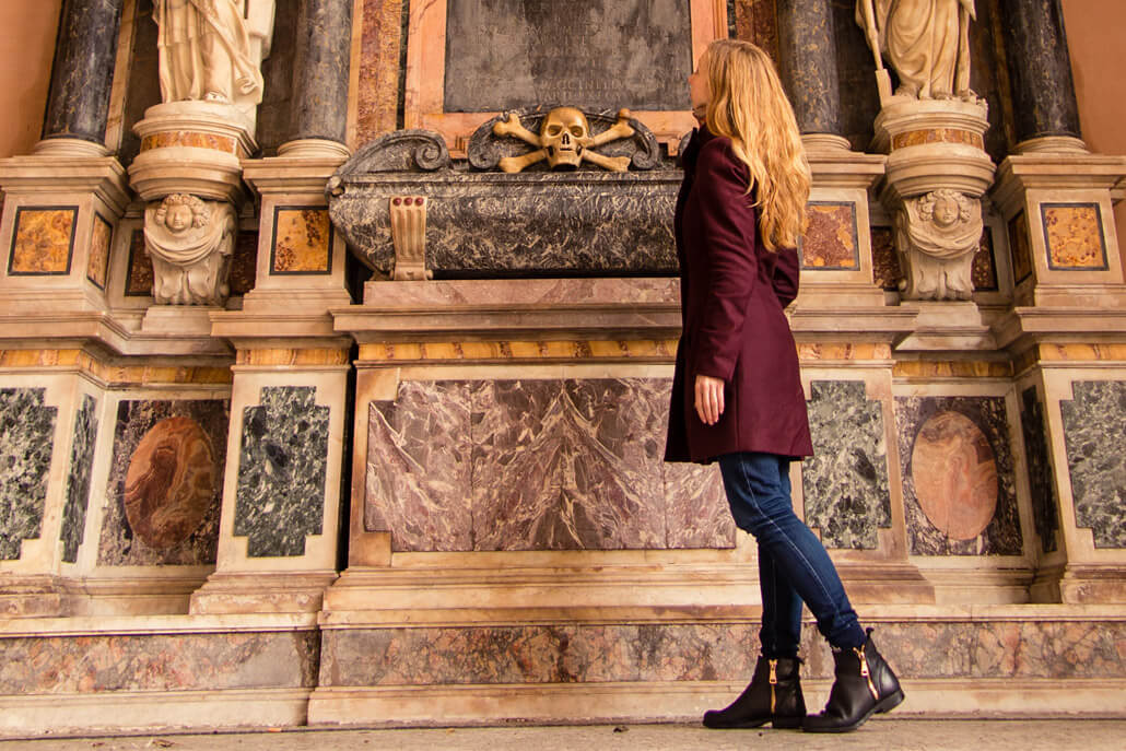 A woman dressed in a coat and leather boots looking at a monument in Rome Italy