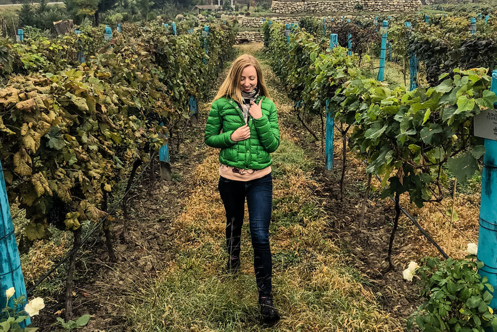 Veronika of TravelGeekery strolling the vineyards of Shumi Winery