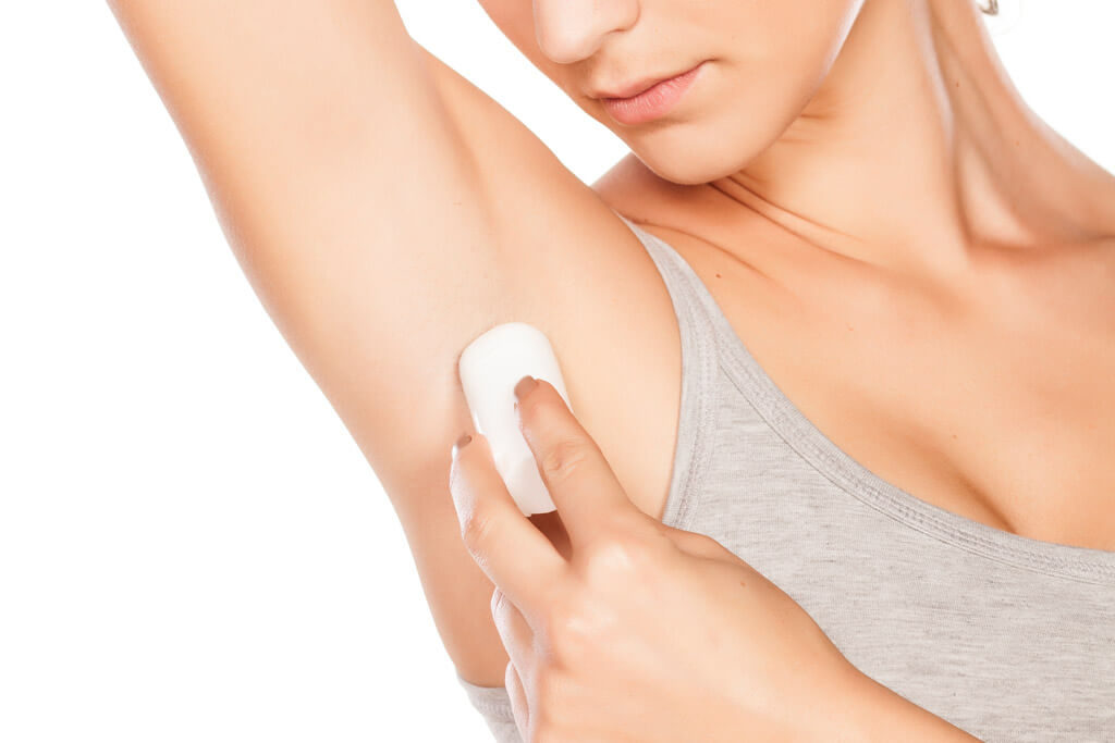 A woman applying a deodorant to her armpit
