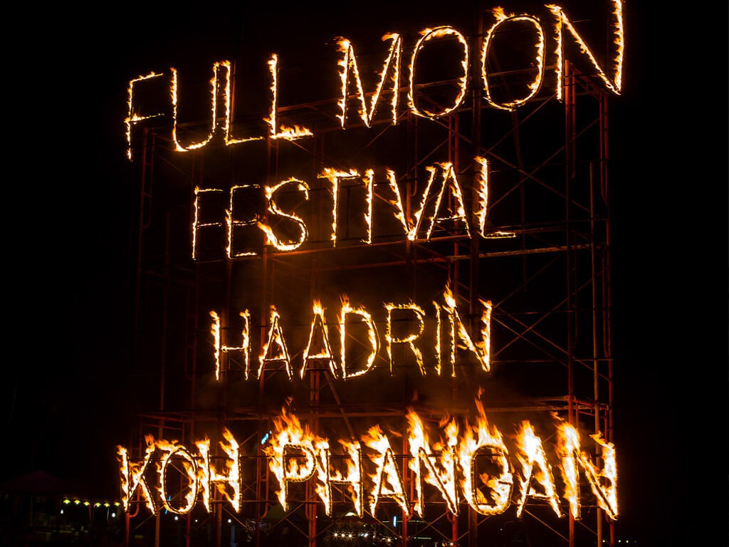 "Sign made out of fire spelling ""Full Moon Festival Haad Rin Koh Phangan"""