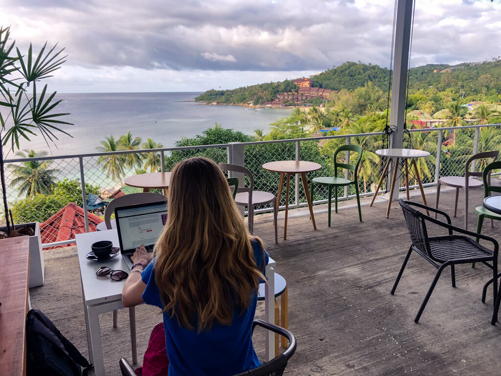 Working at a laptop with a view of the ocean