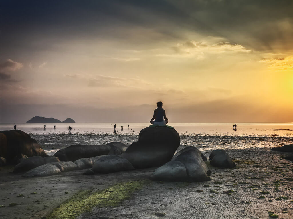 A man meditating on a rock