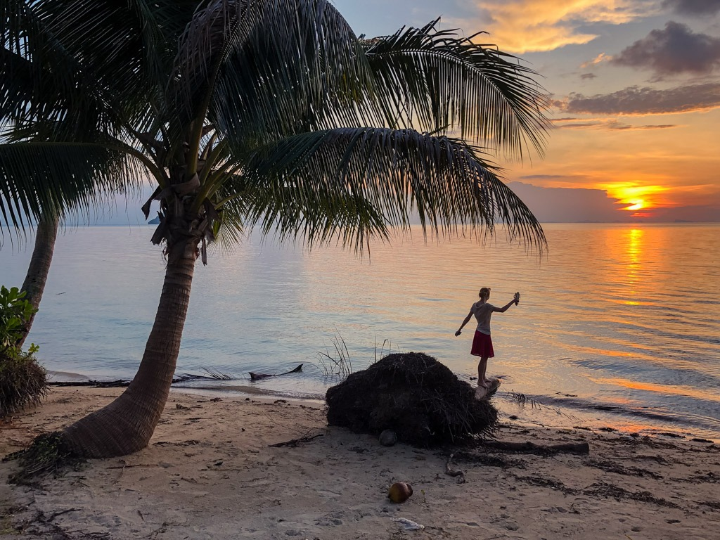 A woman standing on a palm trunk on a beach in Thailand upon sunset (Hinkong Beach, Koh Phangan)