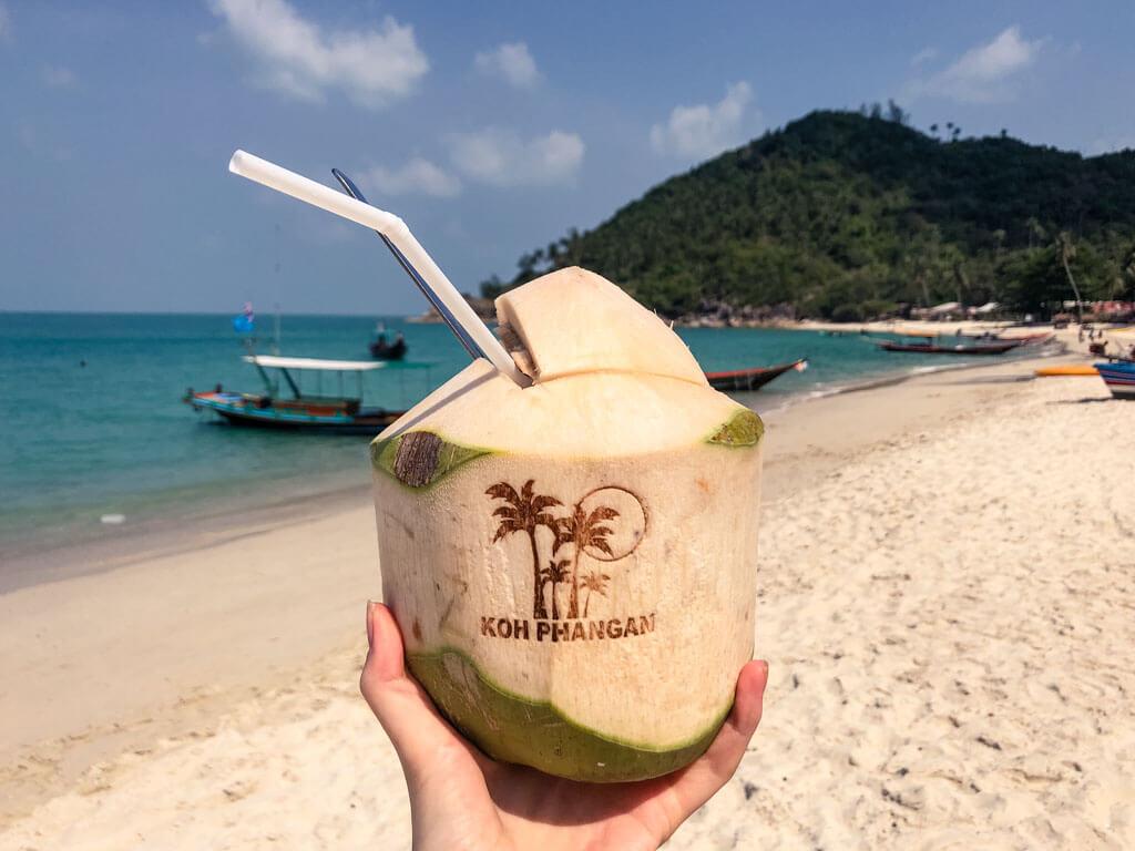 A hand holding a fresh coconut on a beach