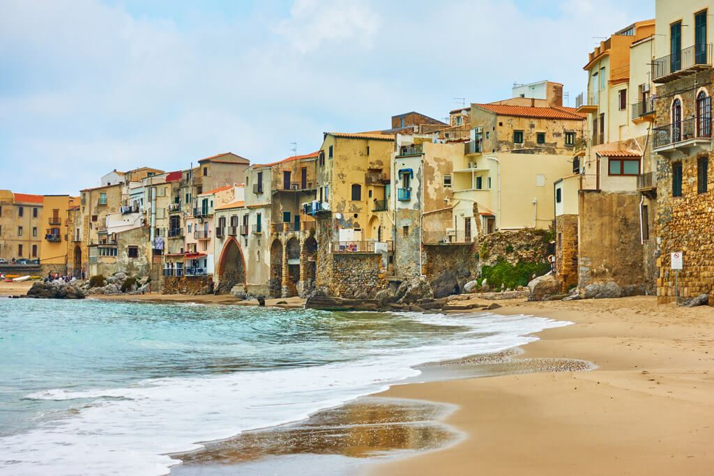View of a beach with old houses in Cefalu, Sicily