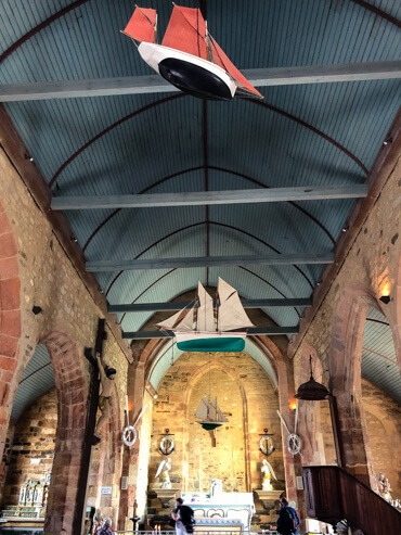 Little boats hanging from the ceiling of a church