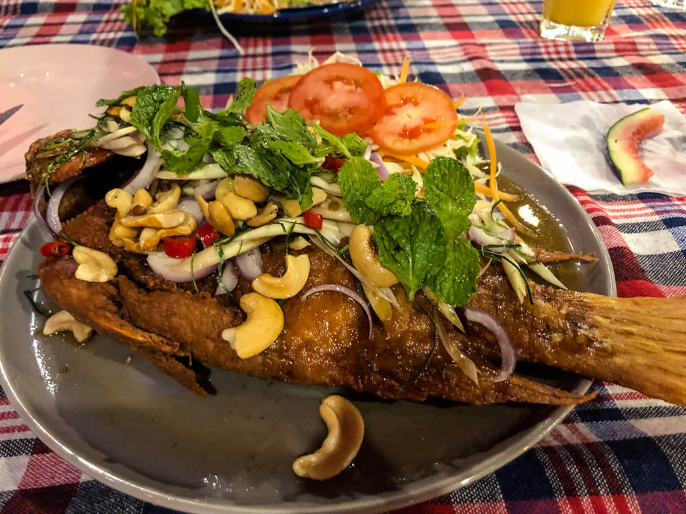 Deep fried fish served with herbs and cashew nuts at a Thai restaurant