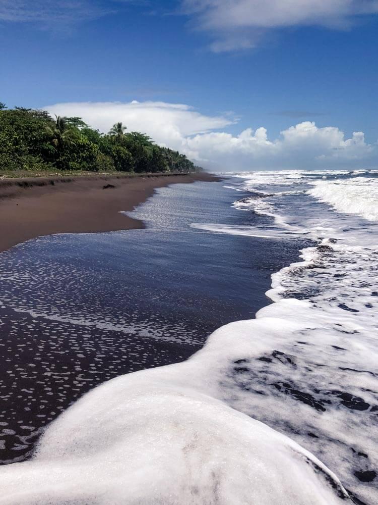 tropical beach with black volcanic sand
