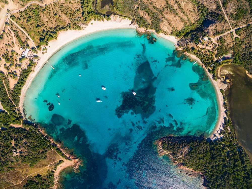 Aerial photo of a moon-shaped white-sand beach in Corsica France