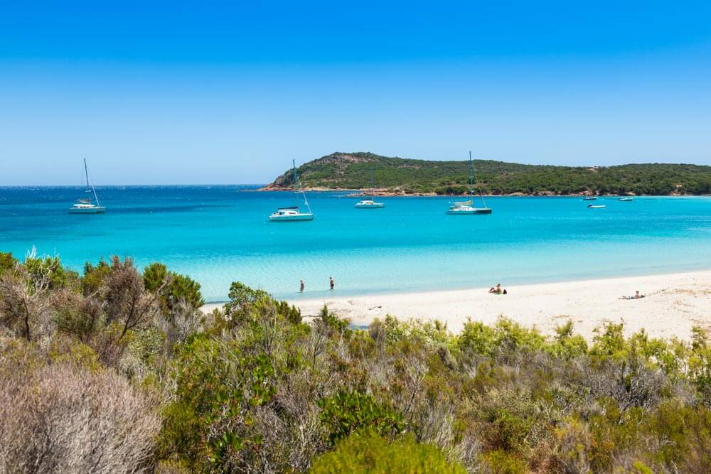Perfect white sand beach in Corsica with yachts