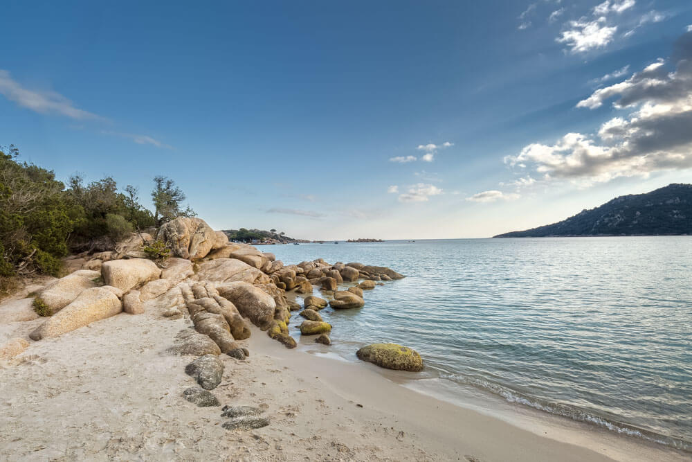 White sand beach with boulders in Corsica France