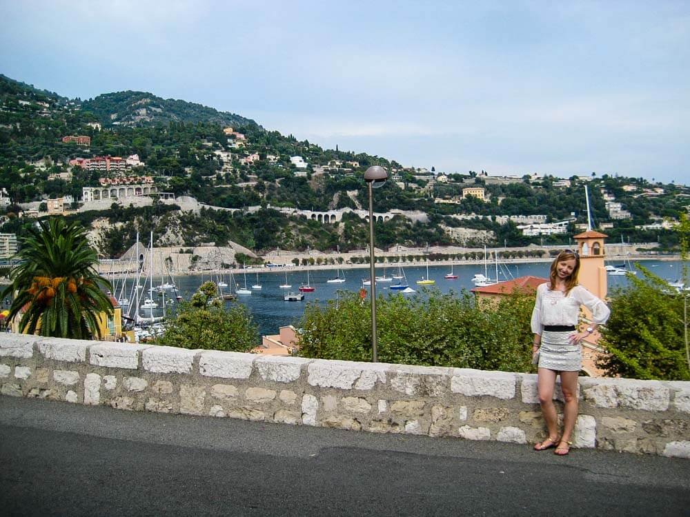 Veronika from Travel Geekery posing with the view of Villefranche, a seaside village in the French Riviera